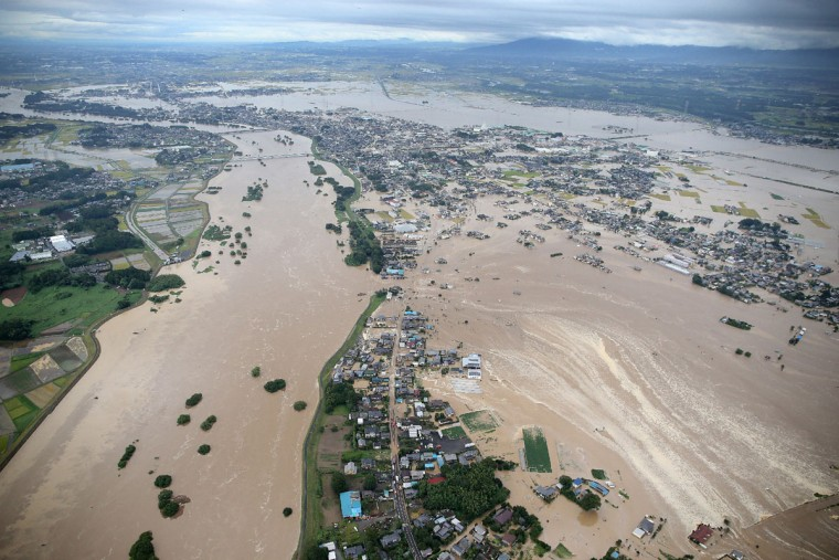 Floodwaters from the burst Kinugawa river (L) flow into a residential area (R) in Joso, Ibaraki Prefecture, on September 10, 2015. The Japanese city 50 km north east of Tokyo was flooded when Kinugawa river burst its banks, destroying homes and cars as desperate residents waited for help, and as thousands of people were ordered to evacuate. (AFP Photo/P /jiji )