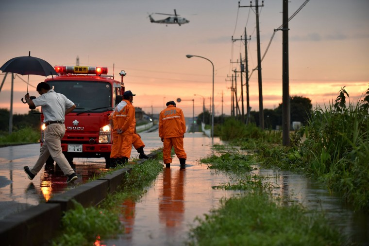 Members of a local fire brigade stand on a flooded street as they watch a rescue operation by helicopters in Joso city in Ibaraki prefecture, north of Tokyo on September 10, 2015. A Japanese city was flooded when a raging river burst its banks, washing away homes and cars as desperate residents pleaded for help, after tens of thousands were ordered to flee their homes following torrential rains. (AFP Photo/Kazuhiro Nogi)