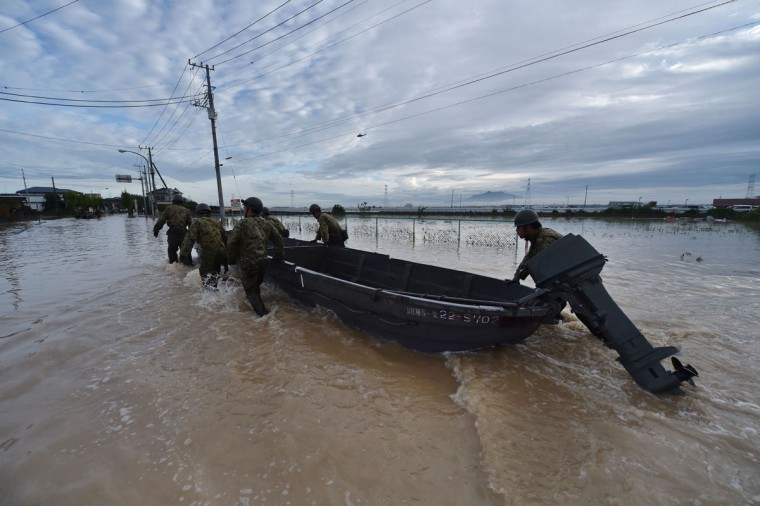 Military servicemen tug a boat as they head to a flooded shopping center to rescue people in Joso city, Ibaraki prefecture, on September 11, 2015. Thousands of rescuers arrived in a deluged city north of Tokyo on September 11 to help evacuate hundreds of trapped residents and search for 12 people missing after torrential rains triggered massive flooding. (AFP Photo/Kazuhiro Nogi)