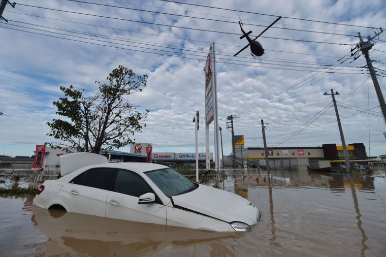 A military helicopter arrives before landing on the roof of a flooded shopping center to rescue people in Joso city, Ibaraki prefecture, on September 11, 2015. Thousands of rescuers arrived in a deluged city north of Tokyo on September 11 to help evacuate hundreds of trapped residents and search for 12 people missing after torrential rains triggered massive flooding. (AFP Photo/Kazuhiro Nogi)