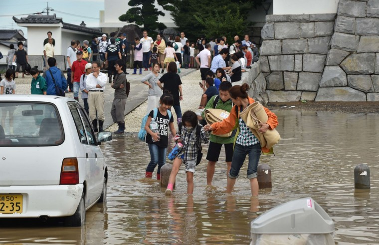 Residents walk on a flooded street after leaving a shelter in the city of Joso in Ibaraki prefecture on September 11, 2015. Thousands of rescuers arrived in a deluged city north of Tokyo on September 11 to help evacuate hundreds of trapped residents and search for 12 people missing after torrential rains triggered massive flooding. (AFP Photo/Kazuhiro Nogi)