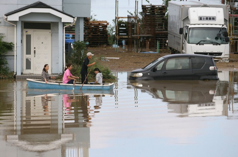 A family is evacuated by boat over floodwaters in the city of Joso in Ibaraki prefecture on September 11, 2015. Thousands of rescuers arrived in a deluged city north of Tokyo on September 11 to help evacuate hundreds of trapped residents and search for 12 people missing after torrential rains triggered massive flooding. (AFP Photo/Jiji japan outjiji press)