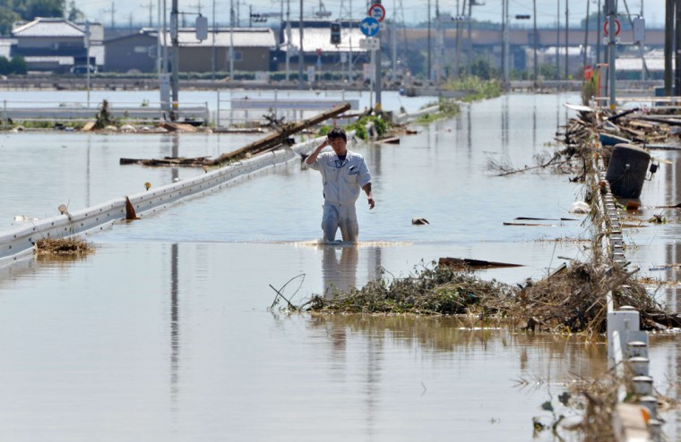A man walks on a road covered by flood waters in the city of Joso in Ibaraki prefecture on September 11, 2015, a day after an embankment of the Kinugawa river collapsed. Thousands of rescuers arrived in a deluged city north of Tokyo on September 11 to help evacuate hundreds of trapped residents and search for 12 people missing after torrential rains triggered massive flooding. (AFP Photo/Yoshikazu Tsuno)