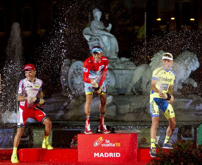 "Winner Astana's Italian cyclist Fabio Aru (C), second Katusha's Spanish cyclist Joaquin Rodriguez (L) and third-placed Tinkoff Saxo's Polish cyclist Rafal Majka spray champagne as they celebrate on the podium of the 70th edition of ""La Vuelta"" Tour of Spain in Madrid on September 13, 2015. (AFP Photo/Jaime Reina)"