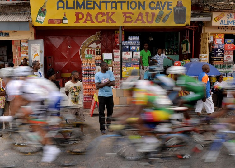 Bystanders look on as the pack of Cyclists competing in 150km cycling final in the the 11th Africa Games ride through an urban area on September 13, 2015 in Brazzaville, Congo. (AFP Photo/Monirul Bhuiyan)