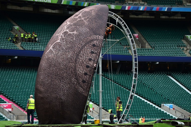 Workers set up the structure for a giant rugby ball on the pitch of the Twickenham Stadium, west London, on September 15, 2015, ahead of the 2015 Rugby Union World Cup. Twickenham Stadium will host the Rugby Union World Cup's opening match between England and Fiji on September 18, 2015. (AFP Photo/Gabriel Bouys)
