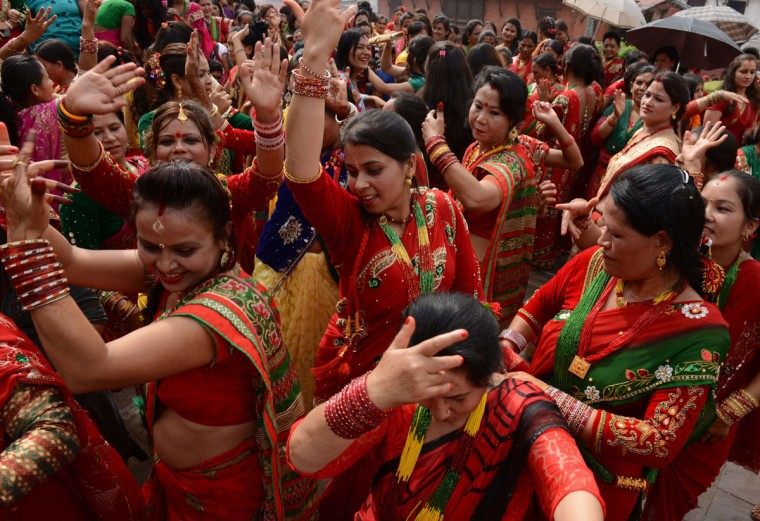 Nepalese Hindu women, dressed in red, dance after paying homage to Shiva, the Hindu god of destruction as they celebrate the Teej festival at the Pashupatinath temple area in Kathmandu on September 16, 2015. The three-day long Teej festival, celebrated by Hindu women in Nepal and some parts of India, is observed by married women with fasting during the day and praying for long lives for their husbands, while unmarried women wish for handsome husbands and happy conjugal lives. (AFP Photo/Prakash Mathema)