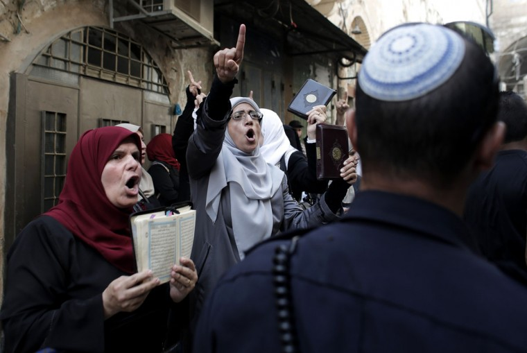 Palestinian women from the so-called Murabitat group shout slogans as they hold copies of the Koran, Islam's holy book, during a protest against Jewish groups visiting the Al-Aqsa mosques compound and against preventing them from entering the shrine in Jerusalem's Old City on September 16, 2015. Palestinians and Israeli security forces clashed in Jerusalem's flashpoint Al-Aqsa mosque compound and the surrounding Old City in the last three days after Israeli forces entered the mosque during the Jewish new year celebrations. (AFP Photo/Ahmad Gharabli)