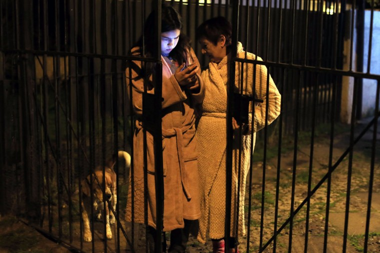Women remain outside a building looking at a mobile phone during a strong quake in Santiago on September 16, 2015. A strong 7.2-magnitude earthquake struck the center of Chile on Wednesday, local seismologists said, triggering a tsunami alert, sparking panic and shaking buildings. (AFP Photo/P )
