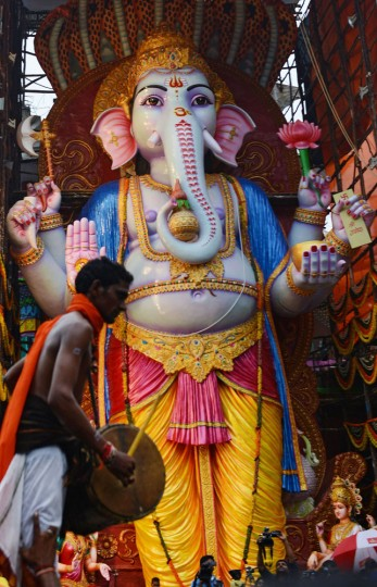 "An Indian Oggu artist (L) perform in front of a 59-foot-tall (18-metre) tall idol of the Hindu god Lord Ganesh, popularly known as ""Khairatabad Ganesh"", on the occasion of the Ganesh Chaturthi Festival in Hyderabad on September 17, 2015. Hindu devotees bring home idols of Lord Ganesh in order to invoke his blessings for wisdom and prosperity during the 11-day long festival, which culminates with the immersion of the idols in water on September 27. (Noah Seelam/AFP/Getty Images)"