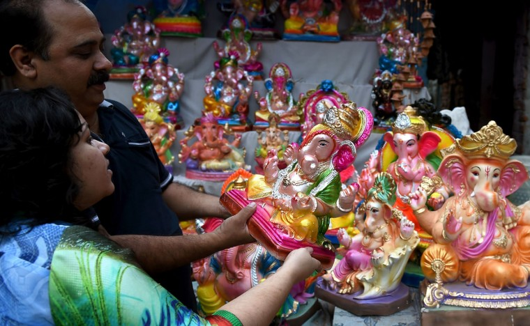 Indian customers choose idols of the elephant headed Hindu God Lord Ganesha at a roadside market in New Delhi on September 17, 2015, at the start of the Ganesh Chaturthi Festival. Hindu devotees bring home idols of Lord Ganesh in order to invoke his blessings for wisdom and prosperity during the 11-day long festival, which culminates with the immersion of the idols in water on September 27. (Money Sharma/AFP/Getty Images)