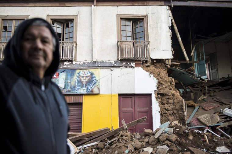 A man crosses a street next to a destroyed house after an earthquake in Illapel, some 200 km north of Santiago on September 17, 2015. A powerful 8.3-magnitude earthquake struck off Chile on September 17, killing eight people, forcing the evacuation of a million and sparking warnings that tsunami waves could reach Japan. (AFP Photo/P )