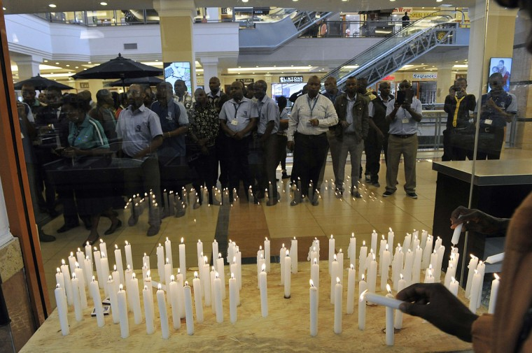 Staff of the Nakumatt supermarket chain gather in front of candles lit to mark the second anniversary commemorations of the Westgate shopping mall attack by militants from Somalia's Al-Qaeda-affiliated Shebab on September 21, 2015 in Nairobi.The attack began on September 21, 2013, when four gunmen entered the mall, spraying shoppers and staff with machine gun fire and tossing grenades into crowds of Saturday shoppers and diners. The attack left 67 dead. (AFP Photo/Simon Maina)