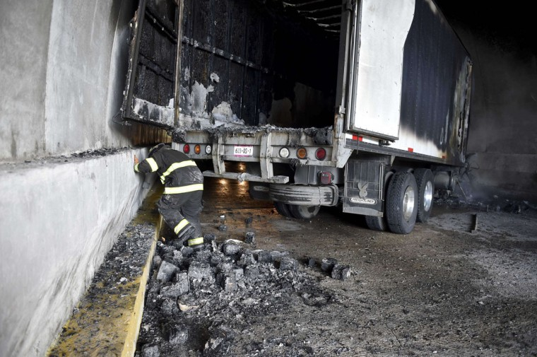 A fireman inspects a truck set ablaze during clashes between student teachers from Ayotzinapa angry for the disappearance of 43 students and the riot police in a tunnel along the Tixtla-Chilpancingo highway in Tixtla, Guerrero State, Mexico, on September 22, 2015. (YURI CORTEZ/AFP/Getty Images)