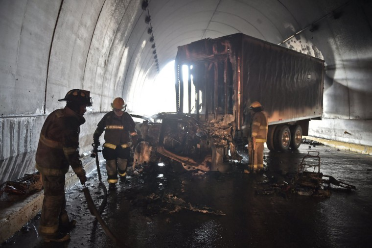 Firemen put down the fire after a truck was set ablaze during clashes between student teachers from Ayotzinapa angry for the disappearance of 43 students and the riot police in a tunnel along the Tixtla-Chilpancingo highway in Tixtla, Guerrero State, Mexico, on September 22, 2015. (YURI CORTEZ/AFP/Getty Images)