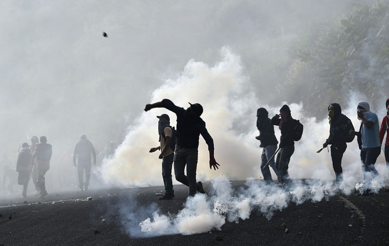 Student teachers from Ayotzinapa angry for the disappearance of 43 students clash with the riot police along the Tixtla-Chilpancingo highway in Tixtla, Guerrero State, Mexico, on September 22, 2015. Its almost a year since the teachers-in-training vanished on the night of September 26-27 in the southern Guerrero state city of Iguala. The fate of 42 of them remains a mystery, only one of the missing students has been confirmed dead. (AFP Photo/Yuri Cortez)