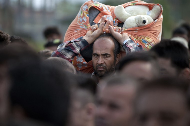 A man carries a bundle with a teddy bear in it as migrants and refugees wait in line to enter a camp after crossing the Greek border into Macedonia near Gevgelija on September 23, 2015. European Union leaders hold an emergency migration summit on September 23 amid a growing east-west split after ministers forced through a controversial deal to relocate 120,000 refugees. (AFP Photo/Nikolay Doychinov)