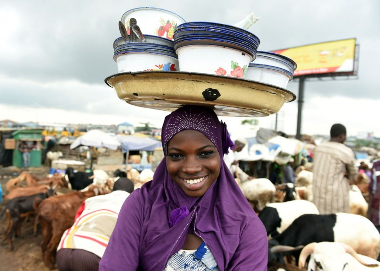 A young vendor hawks food on a market in Kara in the state of Ogun, on September 23, 2015. Nigeria imposed tight movement restrictions in the restive northeast after Boko Haram bombings that killed more than 100 raised fears of fresh attacks over the Eid al-Adha festival. The military said the use of all vehicles would be banned throughout Borno state during the Muslim festival, which is known as Sallah in Nigeria and marked with two days' public holiday from Thursday. (AFP Photo/Pius Ekpeipius Utomi Ekpei)