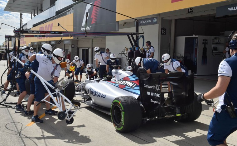 Team members of Williams Martini racing practice tyre change procedures at a pit before the third practice session of the Formula One Japanese Grand Prix at the Suzuka circuit on September 26, 2015. (Kazuhiro Nogi/Getty Images)