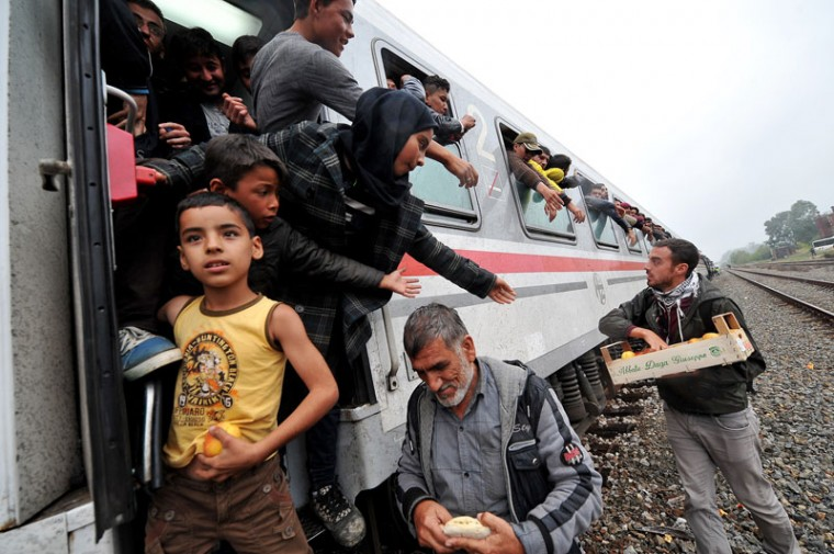 Migrants and refugees are given food by local activists after boarding a train headed for the northern Croatian town of Botovo, after crossing the Serbian-Croatian border near the town of Spacva on September 26, 2015. Nearly 10,000 migrants entered Croatia September 25, a record daily influx since they started entering the country on their journey to seek a new life in western Europe, interior ministry said September 26. The overall number of the migrants who entered the European Union member from neighbouring Serbia during the past 10 days totalled 65,000, an interior ministry statement said. The influx started after Hungary sealed its border with Serbia earlier this month. (AFP Photo/Elvis Barukcic)