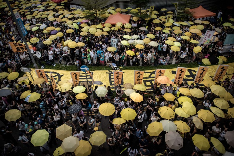 Pro-democracy demonstrators and activists gather outside the government headquarters building to mark one year since the start of mass pro-democracy rallies calling for fully free leadership elections in the semi-autonomous city, in Hong Kong on September 28, 2015. The 2014 Occupy protests began after China's central government claimed it was offering a compromise of sorts by allowing a popular vote for the Hong Kong leader in 2017 but insisted candidates were vetted. (AFP Photo/Philippe Lopez)