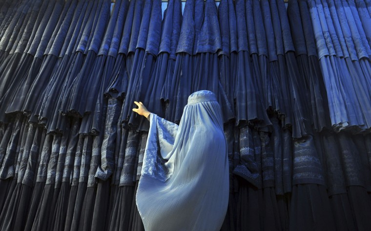 A woman clad in a burqa looks at other pieces of Afghanistan's traditional, all-encompassing dress at a store in Mazar-i Sharif, north of Kabul, Afghanistan, Thursday, Sept. 10, 2015. (AP Photo/Mustafa Najafizada)