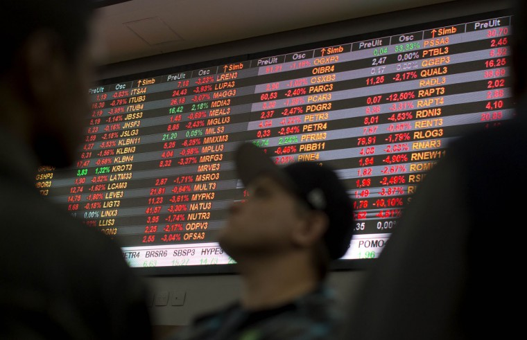 "Visitors look at stock price monitors inside the BM&F BOVESPA stock exchange headquarters in Sao Paulo, Brazil, Thursday, Sept. 10, 2015. Brazil's financial markets fell Thursday in the aftermath of credit agency Standard & Poor's downgrading the country's sovereign debt to ""junk"" status. (AP Photo/Andre Penner)"