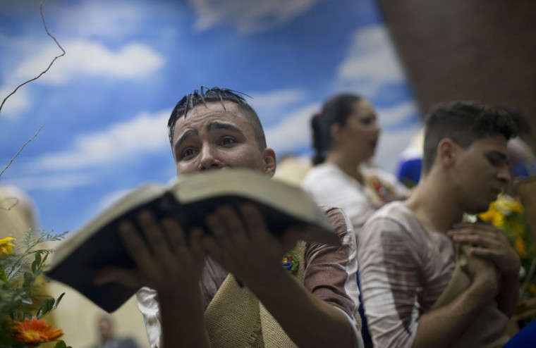 A young devotee performs while holding a Bible during a service at the Contemporary Christian Church in Rio de Janeiro, Brazil, Monday, Sept. 7, 2015. At the Contemporary Christian Church, which on Monday celebrated its ninth anniversary and the opening of its ninth branch with a raucous, theatrical service, homosexuality is celebrated rather than stigmatized. (AP Photo/Silvia Izquierdo)