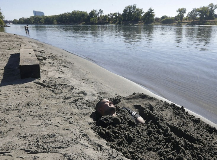 Jose Mureo rests in the sand after burying himself along the Sacramento River as temperatures soared in the mid 90's, Monday, Sept. 21, 2015, in Sacramento, Calif. (AP Photo/Rich Pedroncelli)