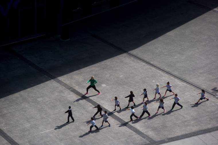 A group of school children exercise on the plaza outside BC. Place stadium in Vancouver, British Columbia, Monday, Sept. 14, 2015. (Darryl Dyck/The Canadian Press via AP)