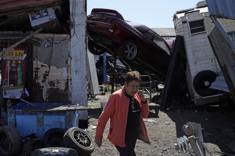 A woman walks past a car propped up between structures among the debris left behind by an earthquake-triggered tsunami in the coastal town of Coquimbo, Chile, Thursday, Sept. 17, 2015. Parts of this port city are a disaster zone after Wednesday night's 8.3-magnitude quake hit off the coast. (AP Photo/Luis Hidalgo)
