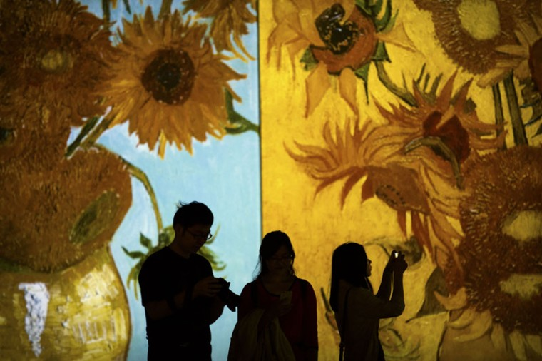 "Visitors take photos as paintings by Vincent van Gogh are projected during an exhibition at a shopping mall in Beijing, Saturday, Sept. 12, 2015. The ""Van Gogh Alive"" exhibit includes over 3,000 images of the Dutch painter's work as part of a multimedia display. (AP Photo/Mark Schiefelbein)"
