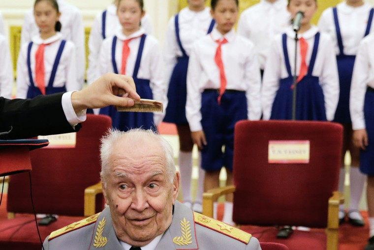 "A Chinese officer helps comb the hair of Russian veteran M.A. Gareev after he arrived for a ceremony to honor veterans of World War II and their family members, at the Great Hall of the People in Beijing Wednesday, Sept. 2, 2015. A total of 30 Chinese and foreign war veterans and their family members who made a contribution to victory of the ""Chinese People's War of Resistance against Japanese Aggression"" received medals from Chinese President Xi Jinping, ahead of the Sept. 3 massive military parade commemorating the end of World War II. (AP Photo/Andy Wong)"