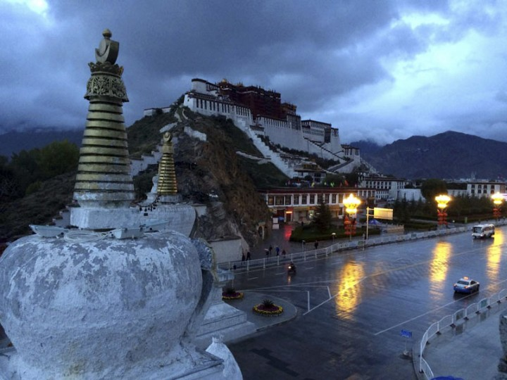 Pedestrians and vehicles make their way past the Potala Palace early on a rainy morning in Lhasa, capital of the Tibet Autonomous Region in China, Saturday, Sept. 19, 2015. Chinese officials have taken foreign journalists on a visit to the region, normally off-limits to them, weeks after Communist Party officials commemorated the 50th anniversary of the establishment of the Tibet Autonomous Region. (AP Photo/Aritz Parra)