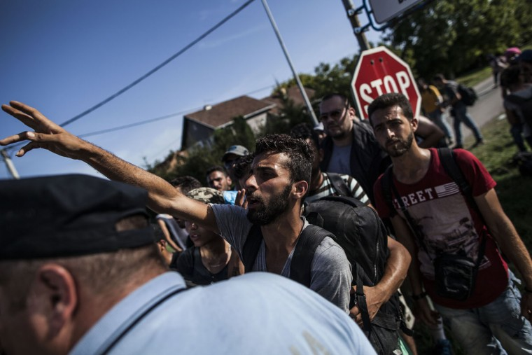 A refugee calls to his friends while trying to get onto a bus at the Tovornik border between Serbia and Croatia, in Tovornik, Croatia, Thursday, Sept. 17, 2015. Croatia has suddenly become the latest hotspot in the 1,000-mile plus exodus toward Western Europe after Hungary sealed off its border Tuesday with a razor-wire fence and then used tear gas, batons and water cannons to keep the migrants out. (AP Photo/Manu Brabo)