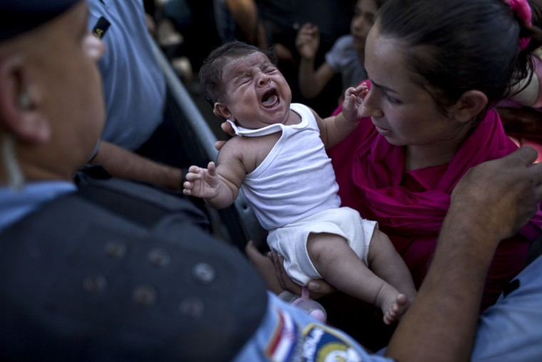 A woman carries a baby as she goes through a police cordon in Tovarnik, Croatia, Thursday, Sept. 17, 2015. Hundreds of migrants have pushed through police lines in the eastern Croatian town of Tovarnik, with people trampling and falling on each other amid the chaos, as more than 2,000 men, women and children were stuck at the local train station for hours in blazing heat and sun on Thursday, waiting to board trains and buses for transport to refugee centers. (AP Photo/Marko Drobnjakovic)
