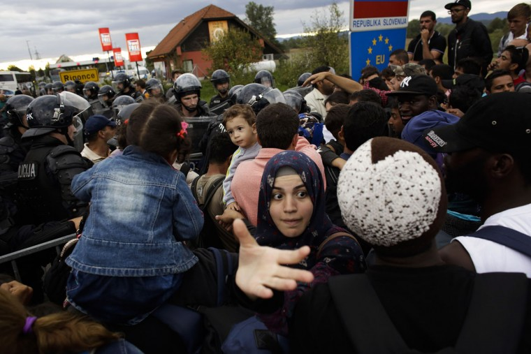 Refugees crowd in front of a line of police officers to cross the border from Croatia to the Slovenian village Rigonce at the border station in Harmica, Croatia, Sunday, Sept. 20, 2015. The refugees enter a bus for transport to a registration center. (AP Photo/Markus Schreiber)