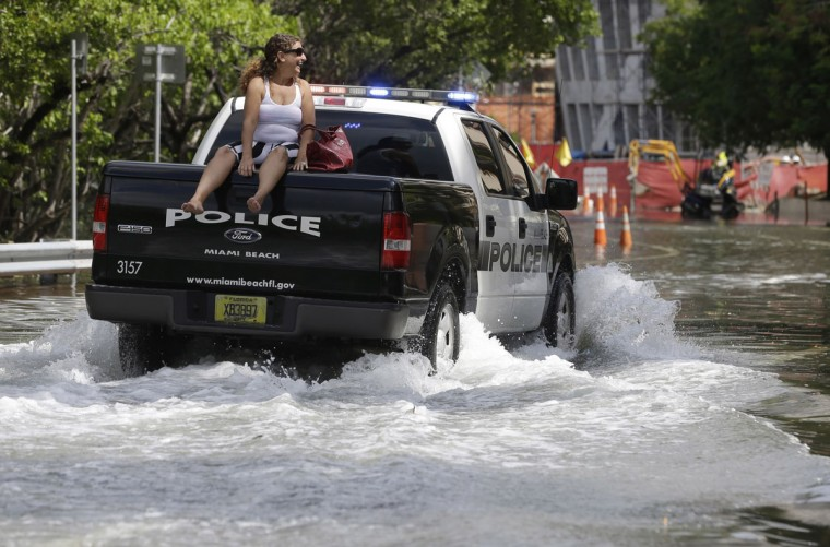 A woman gets a ride on a police truck navigating a flooded Indian Creek Drive, Wednesday, Sept. 30, 2015, in Miami Beach, Fla. The street flooding was in part caused by high tides due to the lunar cycle, according to the National Weather Service. (AP Photo/Lynne Sladky)