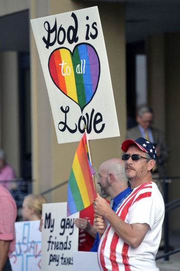 Anthony Carroill of Flat Woods, Ky., waits for the arrival of Rowan County Clerk Kim Davis at the Carl D. Perkins Federal building in Ashland, Ky., Thursday, Sept. 3, 2015. Davis and her deputy clerks have been summoned to a hearing Thursday before Judge David Bunning to explain why she is refusing to issue marriage licenses despite a federal order to do so. (AP Photo/Timothy D. Easley)