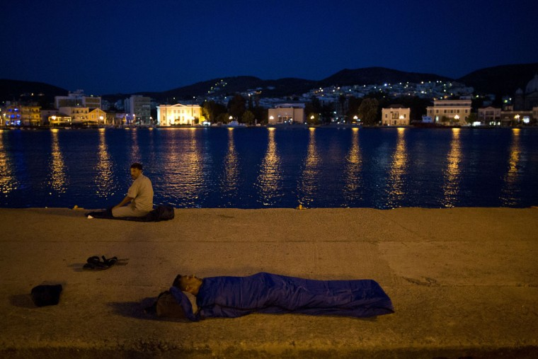 A refugee sleeps on the ground near the port of Mitylene on the northeast Greek island of Lesbos while waiting to get on board a ferry traveling to Athens, Wednesday, Sept. 9, 2015. The head of the European Union's executive says 22 of the member states should be forced to accept another 120,000 people in need of international protection who have come toward the continent at high risk through Greece, Italy and Hungary. (AP Photo/Petros Giannakouris)
