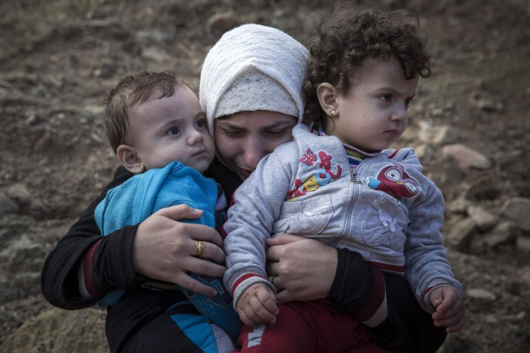 A Syrian mother cries as she hugs her children after spending five hours on a dinghy to approach the Greek island of Lesbos from the Turkish coasts on Wednesday, Sept. 30, 2015. The International Organization for Migration says a record number of people have crossed the Mediterranean into Europe this year, now topping half a million, with some 388,000 entering via Greece. (AP Photo/Santi Palacios)