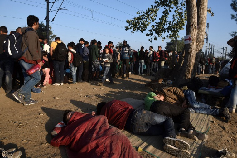 Migrants sleep as others wait at the railway tracks to be allowed to cross the borders from the northern Greek town of Idomeni, to southern Macedonia, Thursday, Sept. 3, 2015. The country has borne the brunt of a massive refugee and migration flow of people heading into the European Union, with more than 200,000 people arriving so far this year. (AP Photo/Giannis Papanikos)