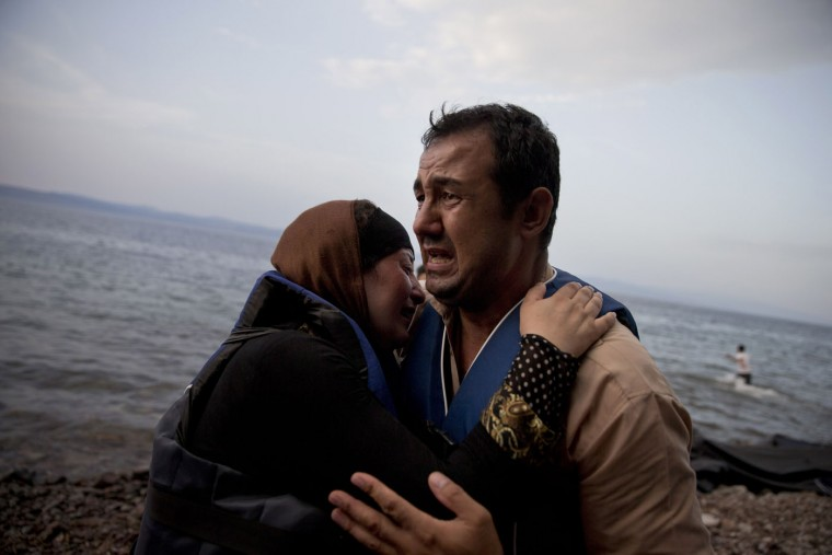 An Afghan woman embraces her husband as they arrive with others migrants from Turkey to Lesbos island, Greece, on a dinghy,Thursday, Sept. 10, 2015. While migrants for years have taken death-defying trips across the Mediterranean to reach the relative peace and comfort of the Europe Union, the flow has hit record proportions this year - notably with an influx of Syrians, Afghans and Eritreans fleeing trouble back home. (AP Photo/Petros Giannakouris)