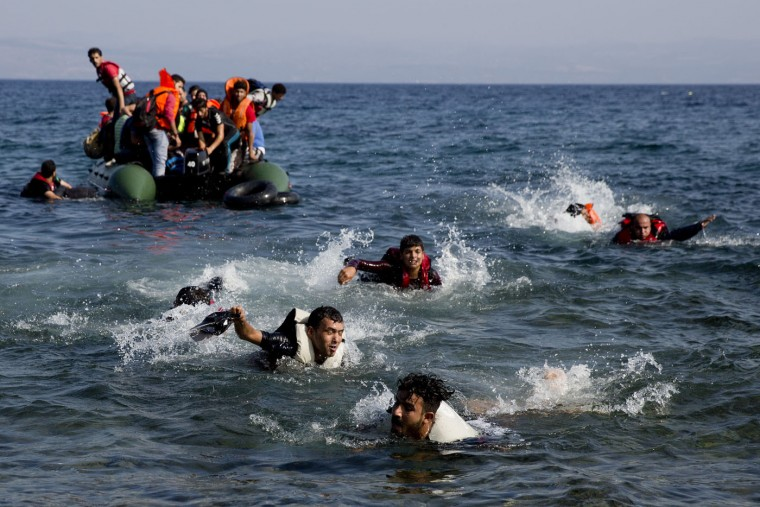 Migrants whose boat stalled at sea while crossing from Turkey to Greece swim to approach the shore of the island of Lesbos, Greece, Sunday, Sept. 20, 2015. A boat with 46 people fleeing Syria sank Sunday in Greece and the coast guard said it is searching for more than 20 others missing off the eastern Aegean island of Lesbos. (AP Photo/Petros Giannakouris)
