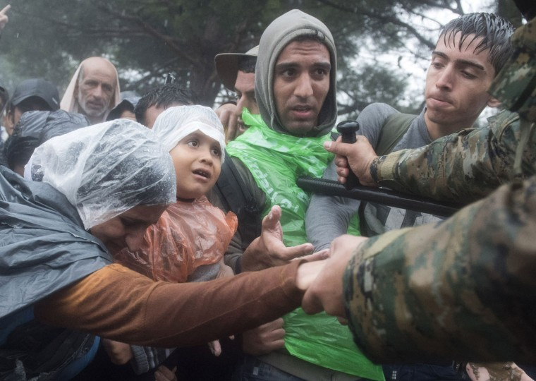 Macedonian border police helps refugees and migrants to pass in heavy rainfall from the northern Greek village of Idomeni to southern Macedonia, Thursday, Sept. 10, 2015. Thousands of people, including many families with young children, braved torrential downpours to cross Greeceís northern border with Macedonia early Thursday, after Greek authorities managed to register about 17,000 people on the island of Lesbos in the space of a few days, allowing them to continue their journey north into Europe. (AP Photo/Giannis Papanikos)