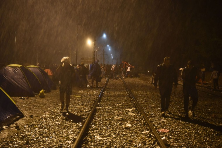 Refugees and migrants walk on the railway tracks in heavy rainfall as they wait to pass from the northern Greek village of Idomeni to southern Macedonia, Thursday, Sept. 10, 2015. Thousands of people, including many families with young children, braved torrential downpours to cross Greece's northern border with Macedonia early Thursday, after Greek authorities managed to register about 17,000 people on the island of Lesbos in the space of a few days, allowing them to continue their journey north into Europe. (AP Photo/Giannis Papanikos)