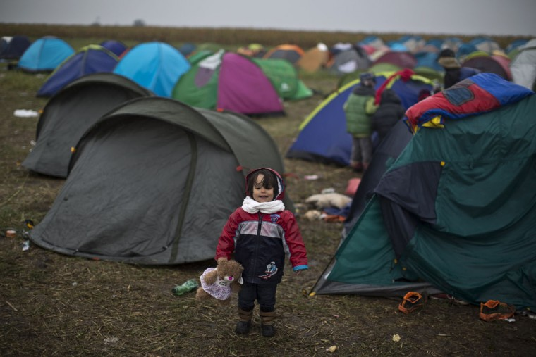 Syrian refugee child Jana Makkiyeh, 3, whose family comes from Damascus, Syria, holds a teddy bear while standing near her family's tent at a makeshift camp for asylum seekers in Roszke, southern Hungary, Thursday, Sept. 10, 2015. Leaders of the United Nations refugee agency warned Tuesday that Hungary faces a bigger wave of 42,000 asylum seekers in the next 10 days and will need international help to provide shelter on its border, where newcomers already are complaining bitterly about being left to sleep in frigid fields. (AP Photo/Muhammed Muheisen)