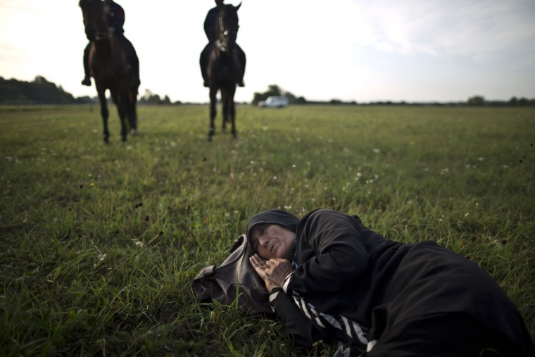 An elderly Afghan migrant rests on the ground of a field while she and others being detained by Hungarian police on horses for sneaking through Hungary's border fence with Serbia, in Asotthalom, southern Hungary, Wednesday, Sept. 16, 2015. Small groups of migrants are continuing to sneak into Hungary from Serbia, a day after the country sealed its border and began arresting asylum-seekers trying to breach the new razor-wire barrier. (AP Photo/Muhammed Muheisen)