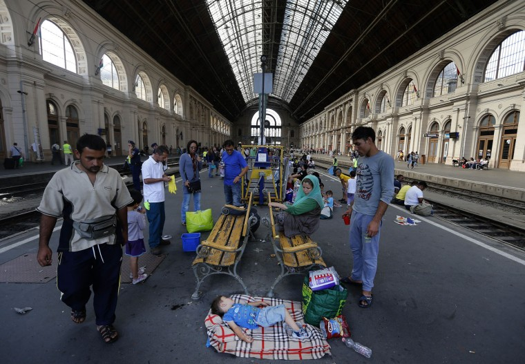 Migrants wait inside the railway station in Budapest, Hungary, Thursday, Sept. 3, 2015. Over 150,000 migrants have reached Hungary this year, most coming through the southern border with Serbia, and many apply for asylum but quickly try to leave for richer EU countries.(AP Photo/Frank Augstein)