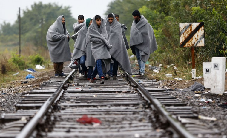 Migrant people cross the serbian-hungarian border at the railway track near Roszke, southern Hungary in Roszke, Thursday, Sept. 10, 2015. Leaders of the United Nations refugee agency warned Tuesday that Hungary faces a bigger wave of 42,000 asylum seekers in the next 10 days and will need international help to provide shelter on its border. (AP Photo/Matthias Schrader)